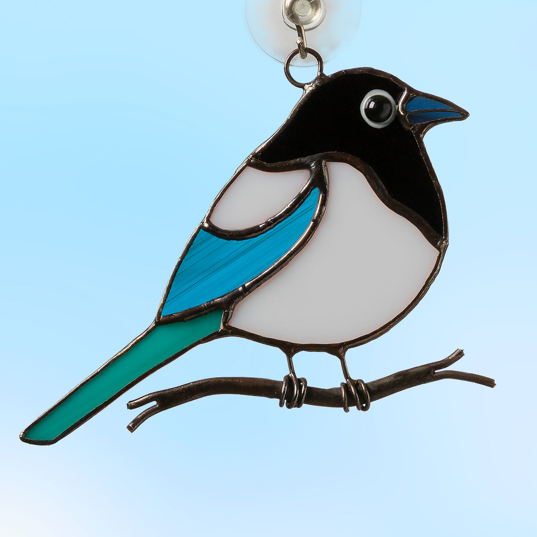 small fat magpie sitting on a branch stained glass suncatcher  Edit alt text