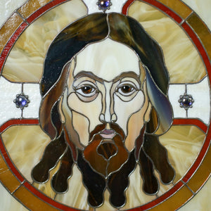 Zoomed stained glass portrait of Jesus Christ in a round with inserted gems panel