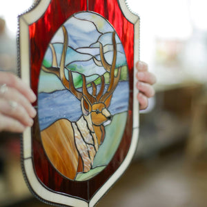 Stained glass panel depicting deer in the forest