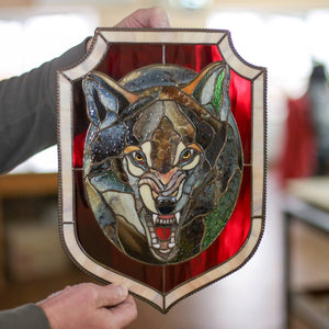 Grey wolf portrait in an oval panel of stained glass