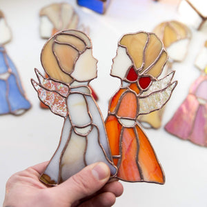 Window hangings of stained glass beige boy and red girl angels