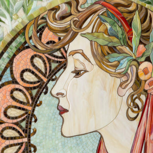 Zoomed stained glass face of a woman in laurel leaves mosaic according to  Alphons Mucha's pattern