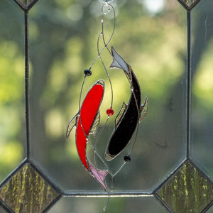 Window hanging of stained glass red and black fishes representing yin yang