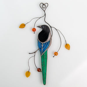 Suncatcher of a stained glass magpie sitting on the branch