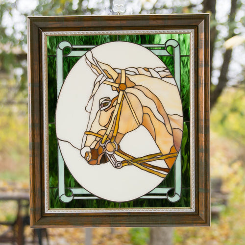 Stained glass horse's head in an oval and green background around it panel in a frame