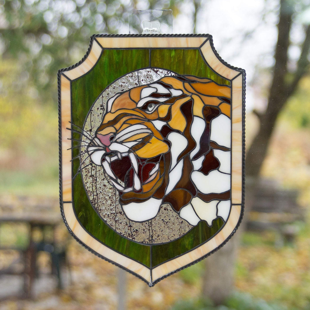 Stained glass panel depicting tiger's head with fangs in an oval and green background