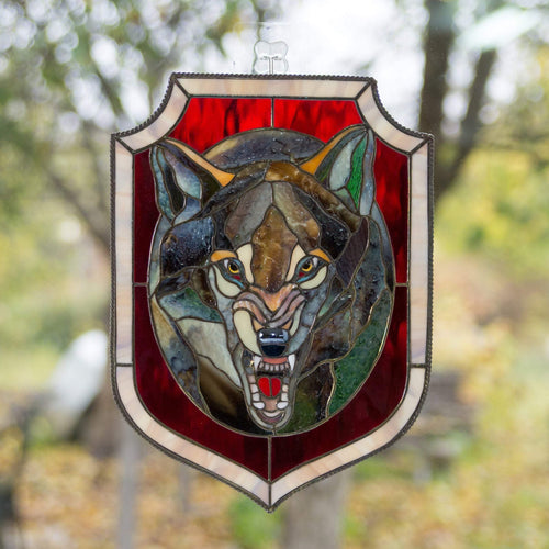 Stained glass grey wolf portrait in an oval with red background window hanging