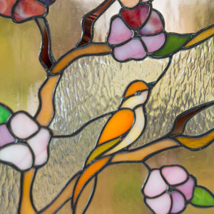 Zoomed stained glass cherry blossom panel with bird depicted on it