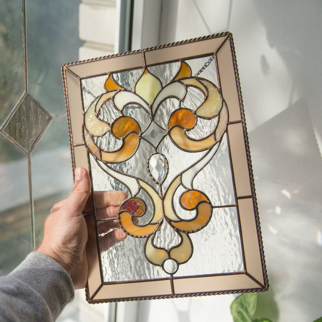 Stained glass clear panel with beige frame and fanciful ornaments