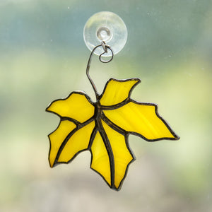 Yellow stained glass suncatcher of a yellow maple leaf