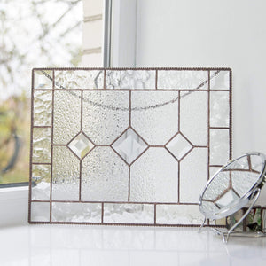 Clear panel of stained glass with three beveled inserts