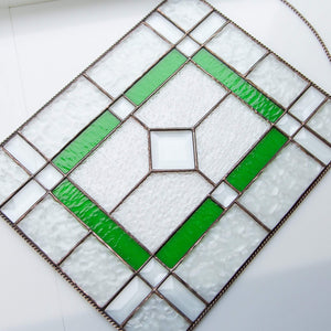 Clear panel of stained glass with green and beveled inserts