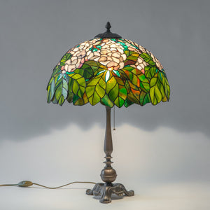 Lit green and white stained glass lamp in Tiffany style