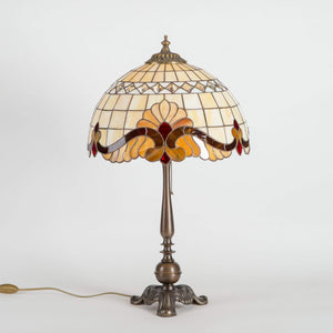 Stained glass Tiffany lamp with red inserts and bronze base