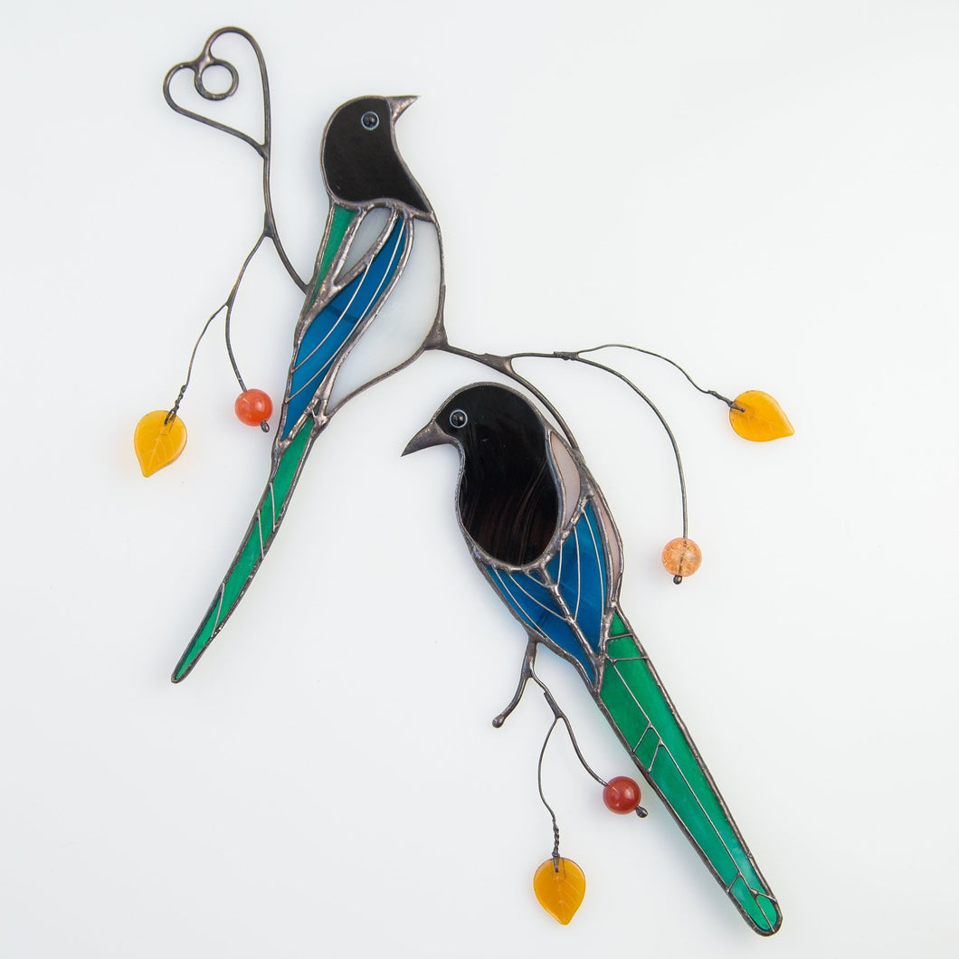 A pair of stained glass magpies sitting on the branch window hanging