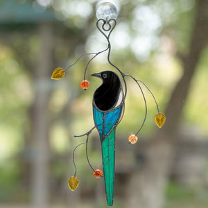 Stained glass colourful magpie sitting on the branch suncatcher