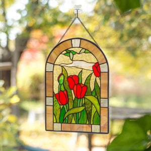 Window hanging of stained glass depicting red tulips with leaves