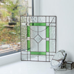 Clear and green panel of stained glass with beveled inserts