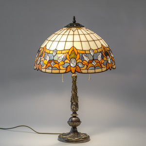 Lit stained glass Tiffany lamp of beige and blue colours
