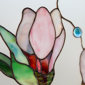Zoomed stained glass magnolia flower on white background window hanging