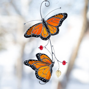 Suncatcher of stained glass monarch butterflies on the branch