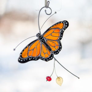 Stained glass monarch butterfly on the branch suncatcher