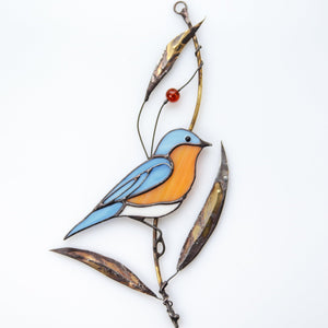 Stained glass bluebird sitting on the branch with bass leaves suncatcher
