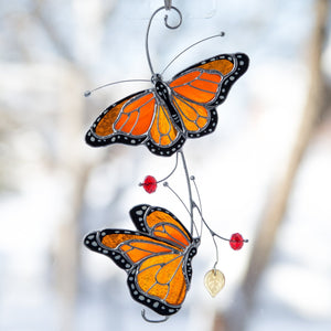 Stained glass suncatcher of orange monarch butterflies siting on the branch