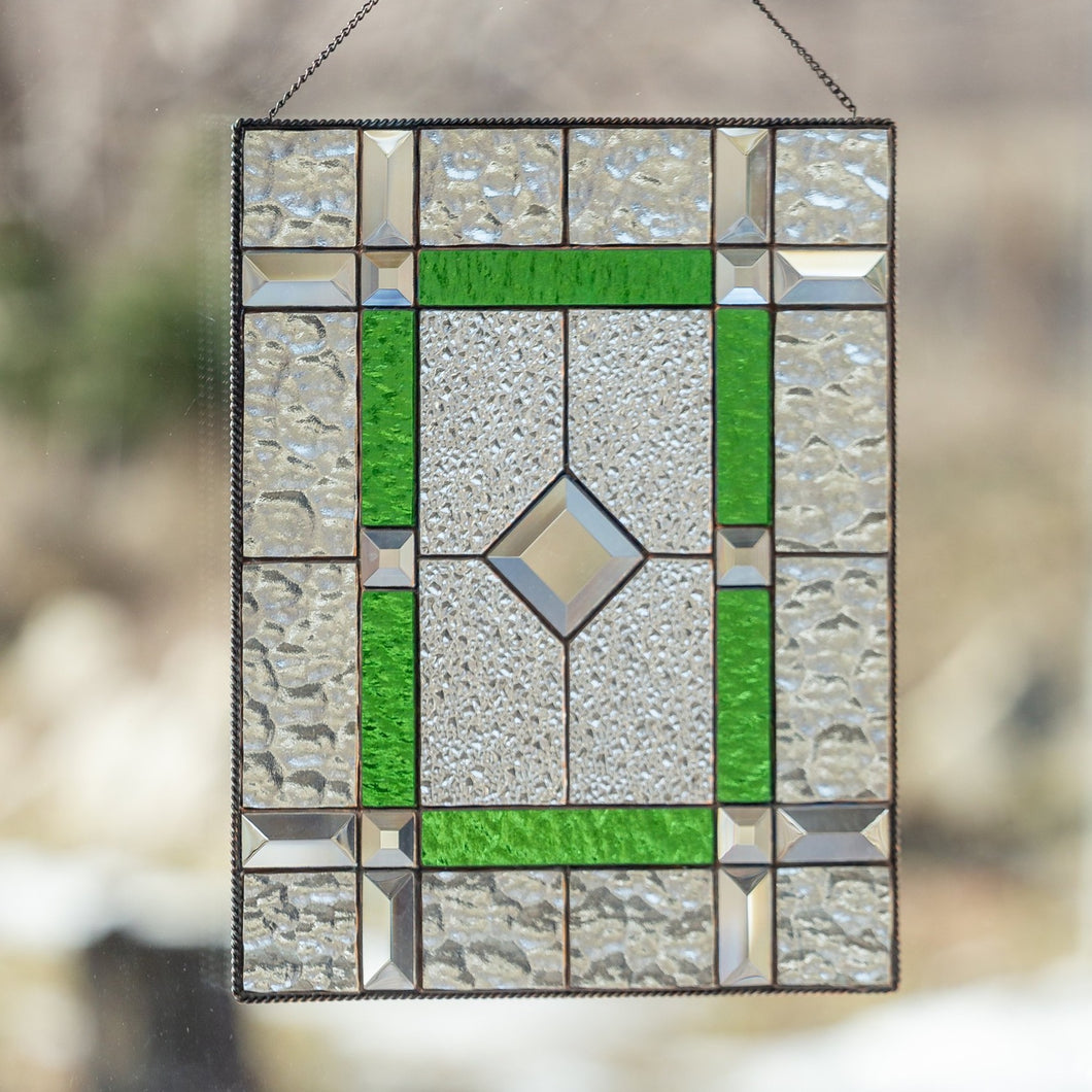Stained glass panel of green colour with beveled inserts
