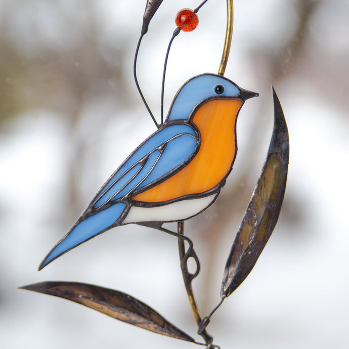 Stained glass suncatcher of a bluebird on the branch with brass leaves