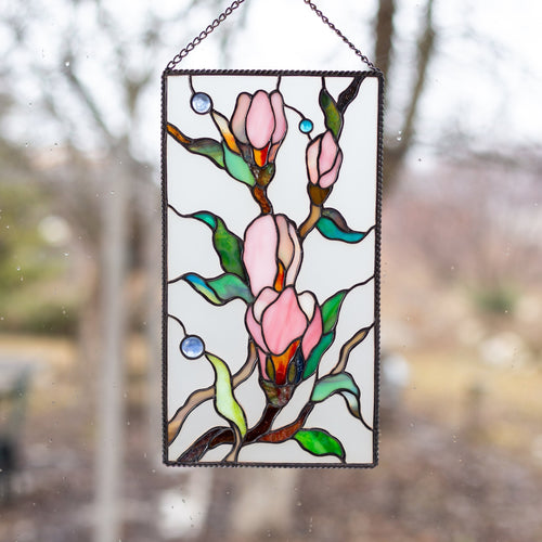 Stained glass magnolia flowers with beveled inserts on the white background panel