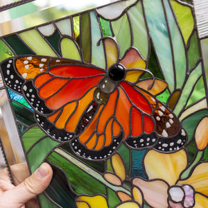 Zoomed stained glass panel depicting monarch butterfly with yellow orchid
