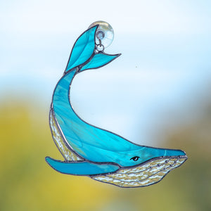 Stained glass whale of a light blue colour with its tail up suncatcher for window decoration