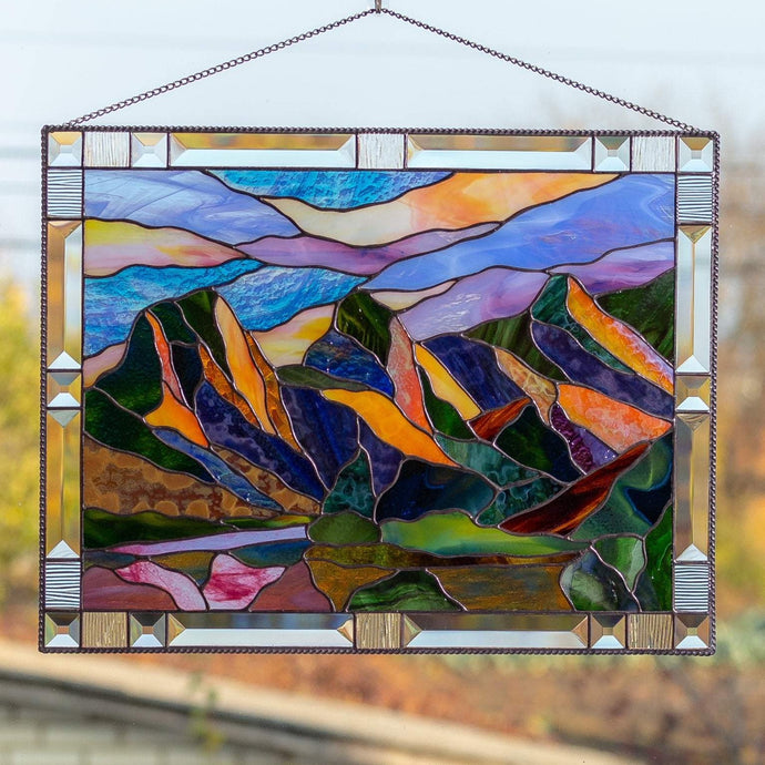 Stained glass panel depicting Three Sisters Mountains with sky of different shades
