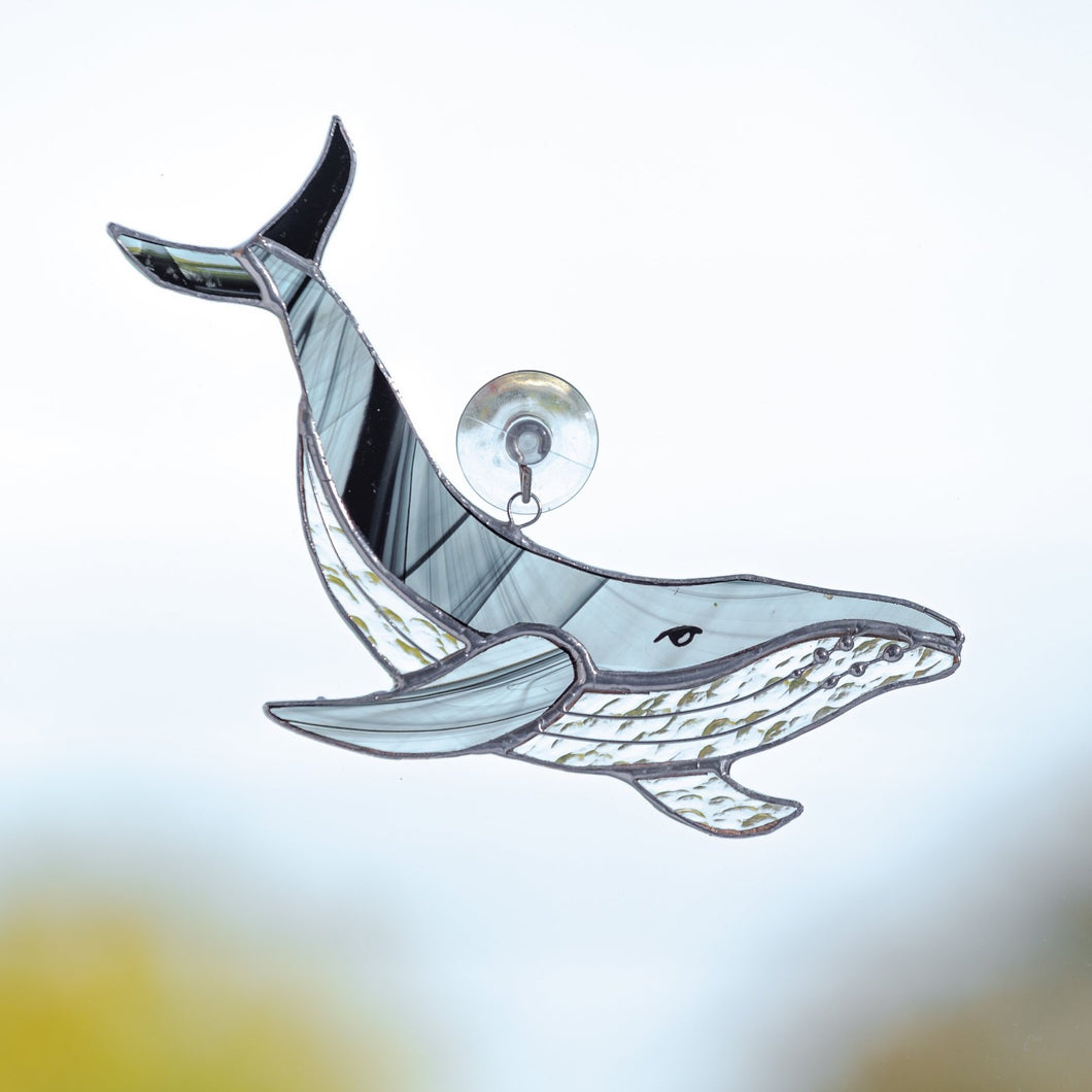 Stained glass suncatcher of a black and grey whale with clear lower part and its tail up