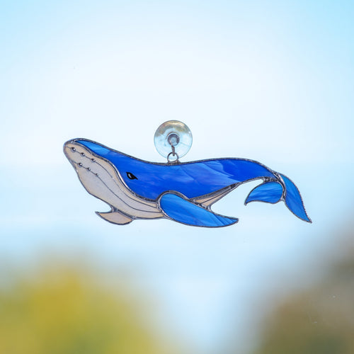 Stained glass royal blue suncatcher of a whale with tail down for window decoration