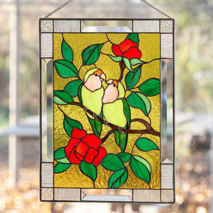 Stained glass panel depicting lovebirds on the branch with red flowers on the yellow background