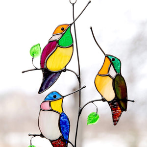Zoomed stained glass hummingbirds sitting on the vertical branch suncatcher