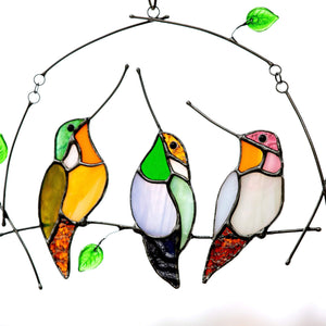 Three zoomed stained glass hummingbirds sitting on the horizontal branch suncatcher