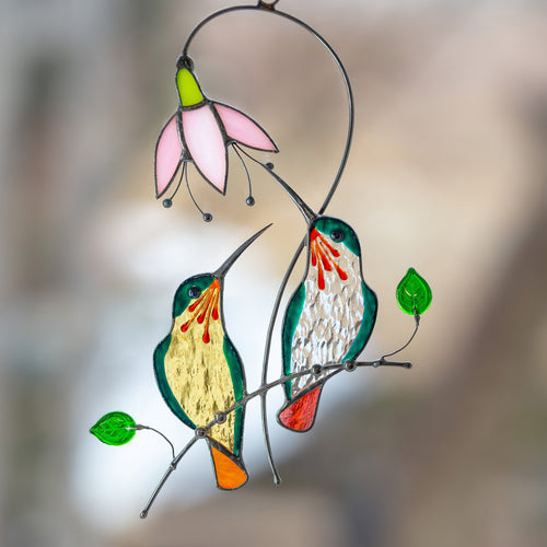 Stained glass green hummingbirds from orange and clear glass sitting on the branch with pink flower suncatcher