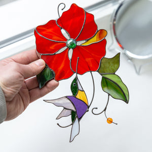 Suncatcher of a stained glass hummingbird with red flower above it