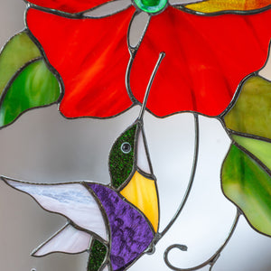 Zoomed stained glass hummingbird and red flower above it suncatcher