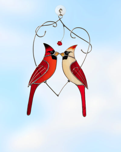 Stained glass suncatcher of red northern cardinals' kissing pair sitting on the heart cooper branch