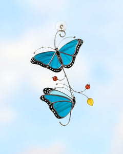 stained glass suncatcher of Blue Morpho butterflies on the branch