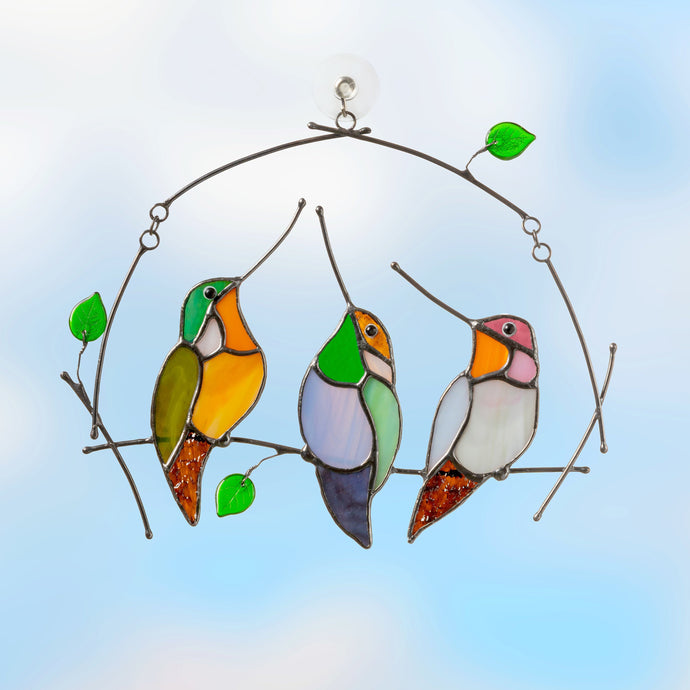 Three stained glass colourful hummingbirds sitting on the horizontal branch suncatcher