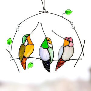 Sitting on the horizontal branch three stained glass hummingbirds suncatcher