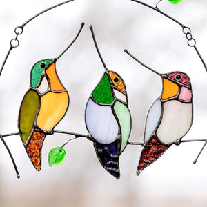 Three zoomed stained glass hummingbirds sitting on the branch window hanging