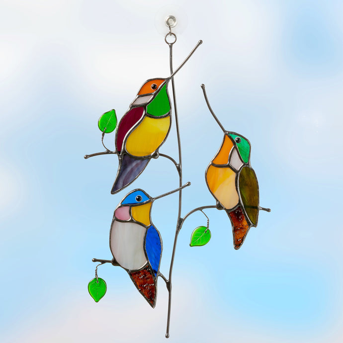 Three stained glass hummingbirds sitting on the vertical branch window hanging