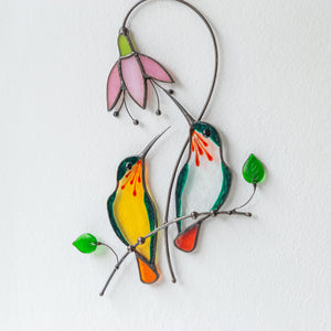 Suncatcher of a stained glass pair of orange and clear glass hummingbirds with pink flower