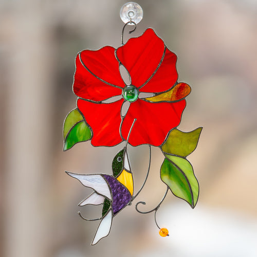 Stained glass hummingbird flying towards red flower suncatcher
